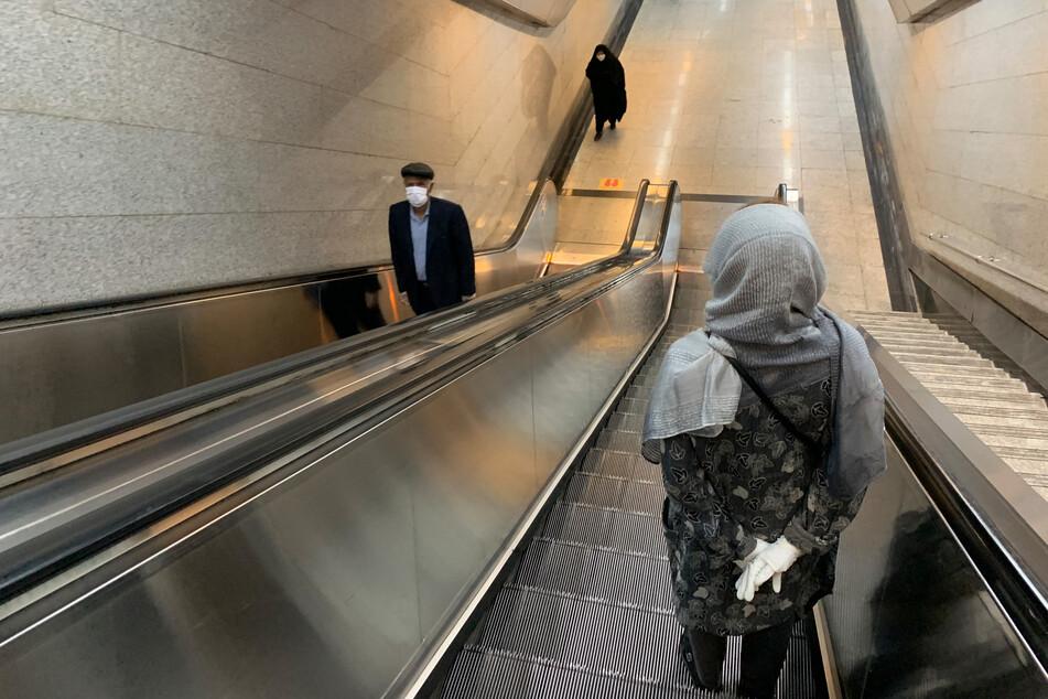 Menschen stehen auf der Rolltreppe der U-Bahn Station Tadschrisch.