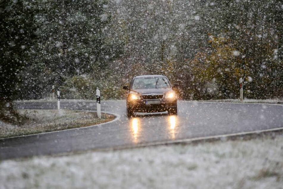Ein Auto fährt durch den Schneefall auf der L275 nahe Landenenslingen.