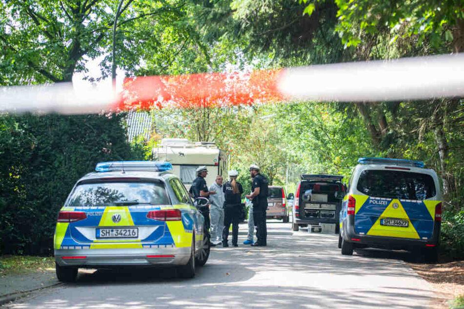 Polizisten stehen vor einem Wohnhaus, in dem die Leiche der Frau gefunden wurde.
