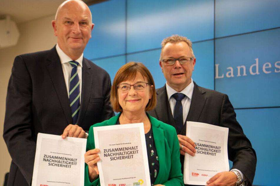 Dietmar Woidke (l.),Ursula Nonnemacher, und Michael Stübgen halten nach einer Pressekonferenz zur Vorstellung des neuen Koalitionsvertrags die ausgedruckten Exemplare des Vertrags in den Händen. (Archivbild)