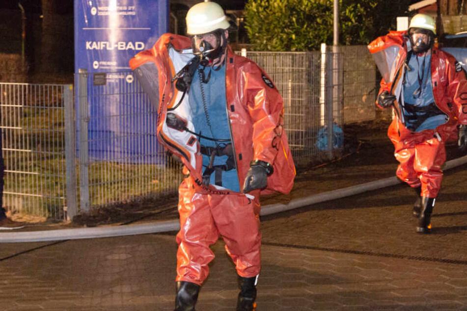 Zwei Einsatzkräfte in Schutzanzügen verlassen das Kaifu-Bad.