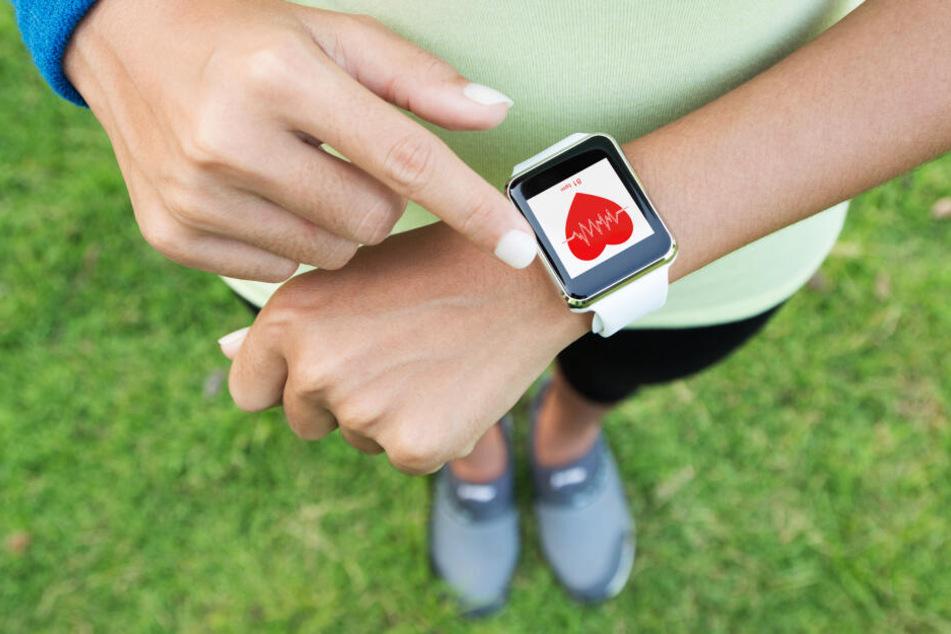 Eine Frau nutzt eine App zur Überwachung der Herzfrequenz beim Sport (Symbolbild).