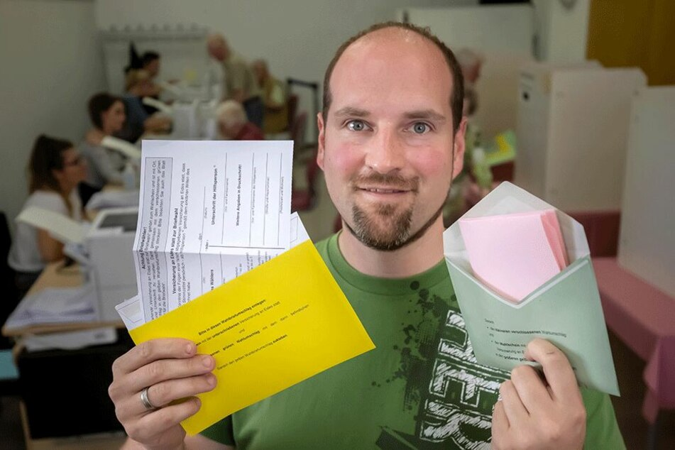 Briefwahlchef Matthias Schieck (37) zeigt die Umschläge: Grün für den Wahlzettel, gelb für die Versicherung.