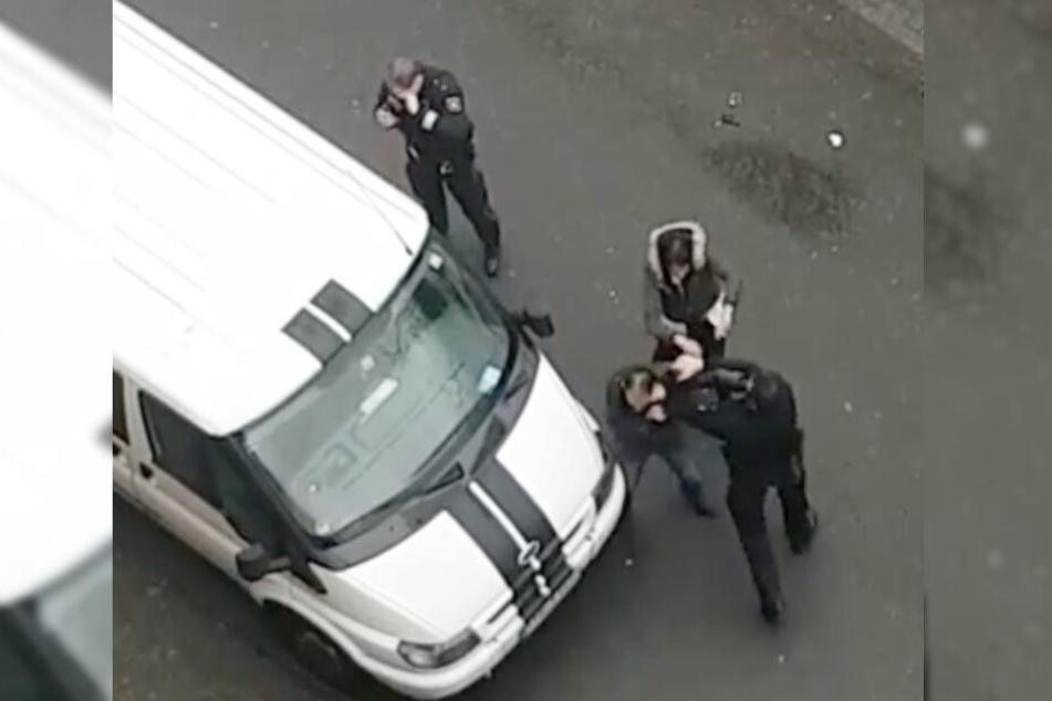 Der Polizist und der Mann schlagen aufeinander ein.