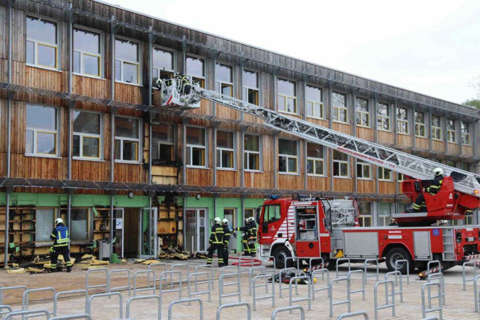 Das Ausmaß des Feuers ist am Gebäude der Schule deutlich zu sehen. Die Einsatzkräfte mussten die Holzverkleidung lösen.