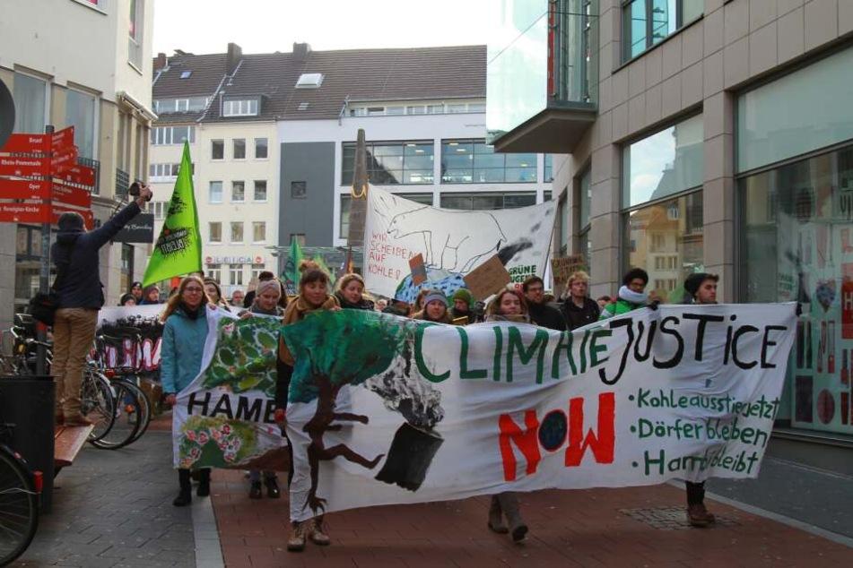 """Auf einem Banner steht """"Climate justice now""""."""