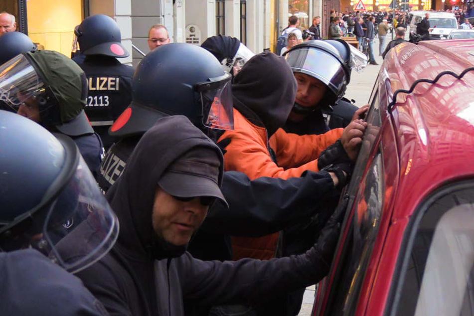 Demo-Teilnehmer werden von der Polizei kontrolliert.