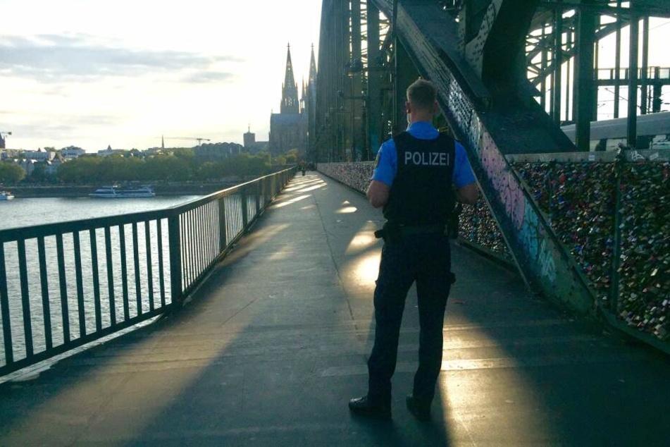 Ein Polizeibeamter bewachte die abgesperrte Hohenzollernbrücke. Der Bahnverkehr wurde nicht gestoppt.