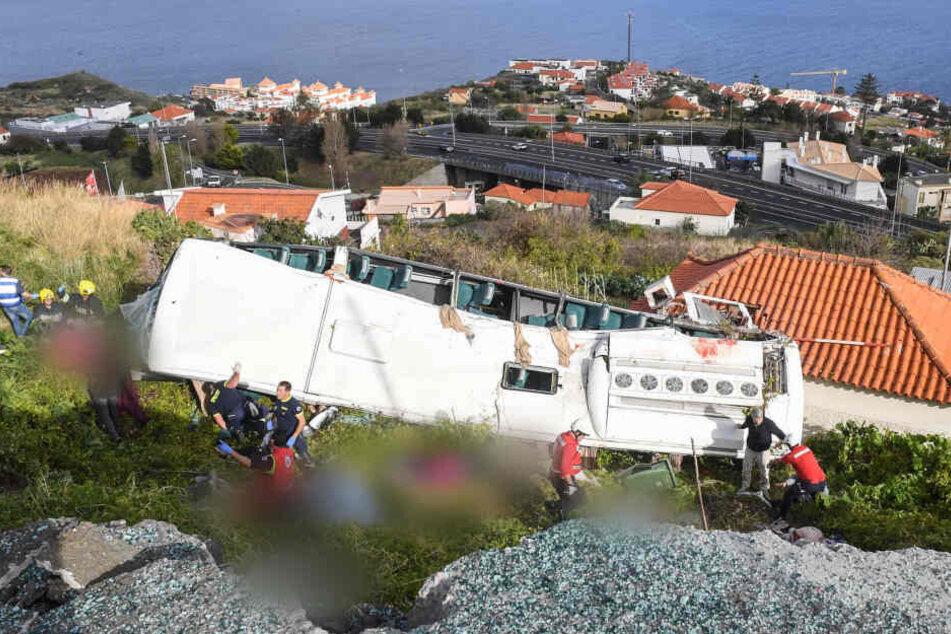 Rettungskräfte stehen nach einem schweren Busunglück auf der portugiesischen Ferieninsel Madeira an dem Bus.