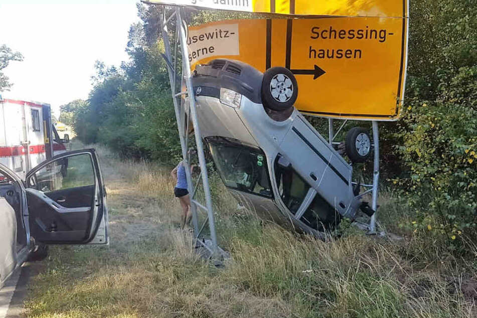 Auto bleibt kopfüber in Straßenschild stecken