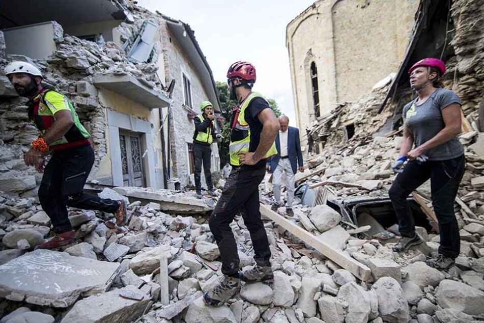 Helfer suchen in den Trümmern nach Überlebenden.