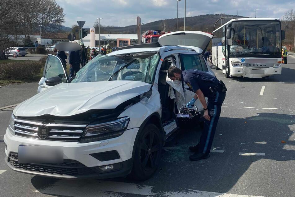 Ein Polizist sichert Spuren am demolierten Unfallwagen.