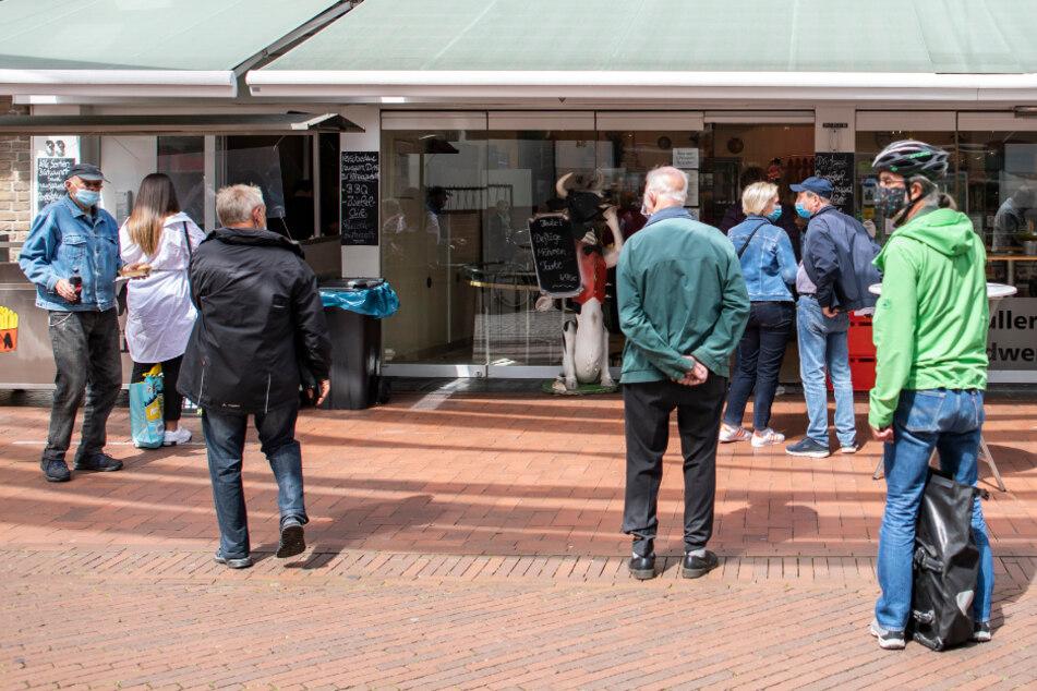 Menschen stehen in der Mittagszeit vor einem Feinkostgeschäft Schlange. Das nordrhein-westfälische Oberverwaltungsgericht hatte die Corona-Beschränkungen für das öffentliche Leben im Kreis Gütersloh am Montag vorläufig außer Vollzug gesetzt.
