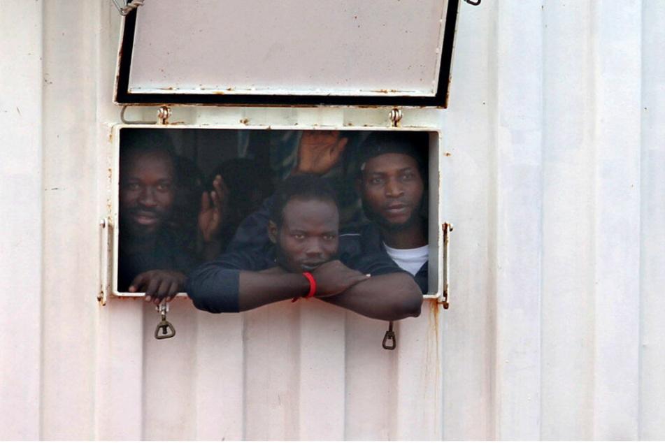 Migranten blicken aus der Öffnung eines Containers an Bord eines Rettungsschiffes. (Archivbild)