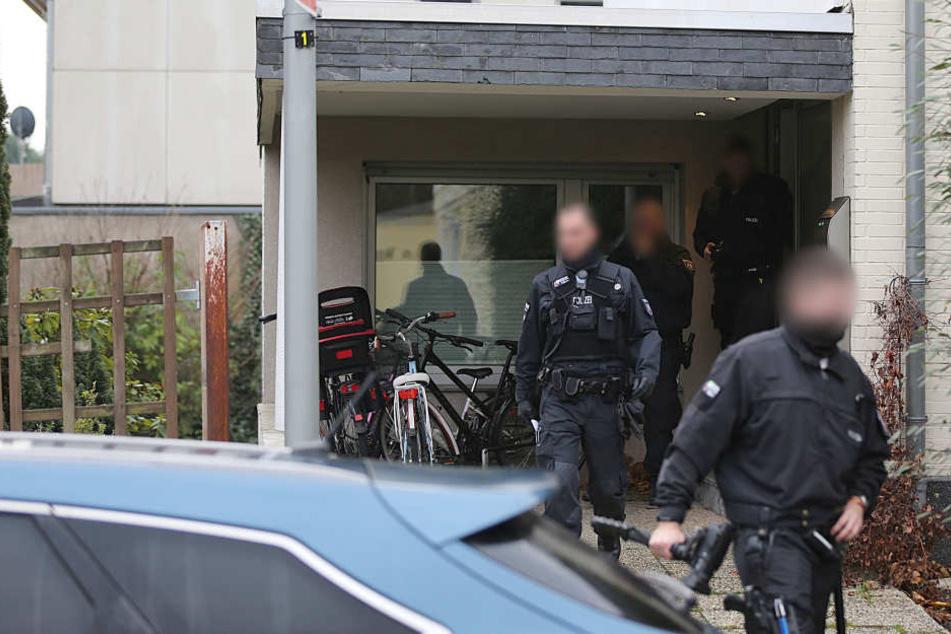 Polizisten verlassen das Wohnhaus eines Italieners.