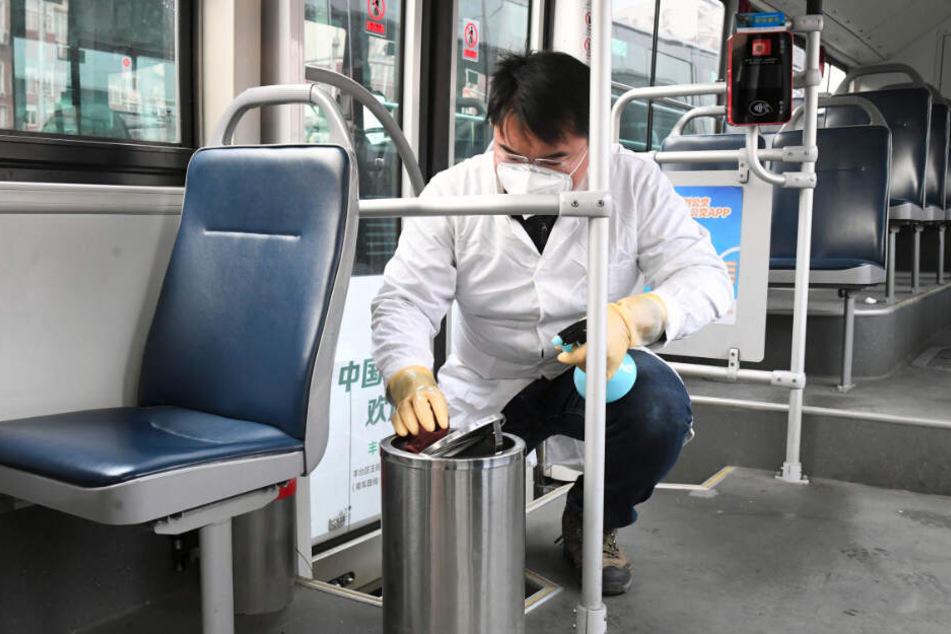 """Ein Mitarbeiter des Verkehrsdienstes """"Beijing Public Transport Corporation"""" führt in Peking Desinfektionsarbeiten in einem Bus am Busbahnhof durch."""