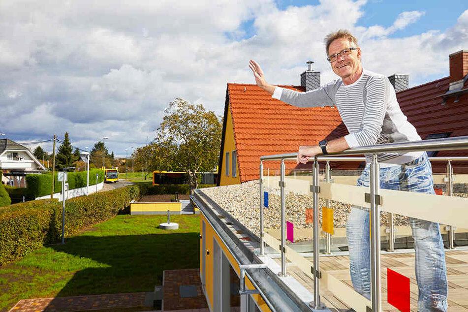 Frank (65) winkt von der Dachterrasse seinem Zwillingsbruder Wolle im gegenüberliegenden Haus zu.