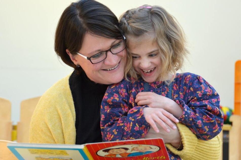 Frieda liest mit Mama Yvonne ein Buch.