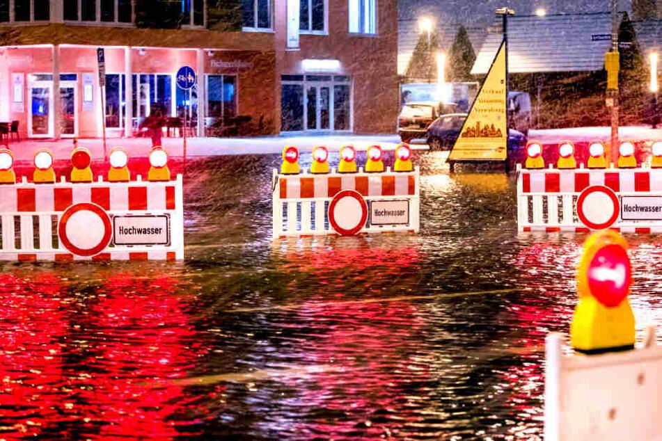 Absperrungen stehen in Wismar auf einer  überfluteten Straßenkreuzung am Stadthafen.
