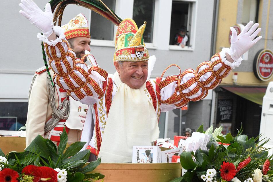Karnevalsprinz Christian II. (57) winkt beim Rosenmontagszug den Menschen zu.