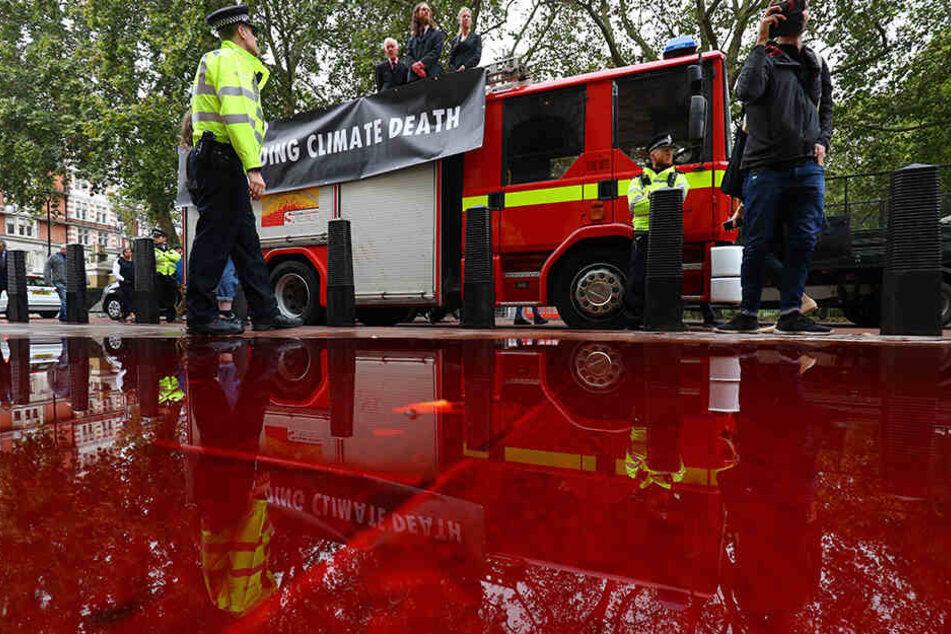 Die Klima-Aktivisten rückten mit einem ausgemusterten Feuerwehrauto im Regierungsviertel an und richteten einen Schlauch auf das Gebäude.