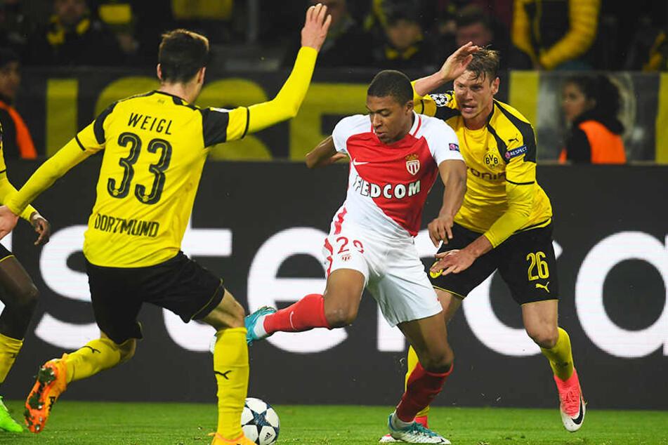 Kylian Mbappé (M.) debütierte bereits mit 17 Jahren beim AS Monaco in der Champions League. Die Dortmunder Julian Weigl (l.) und Lukasz Piszczek (r.) können ihn nicht stoppen.