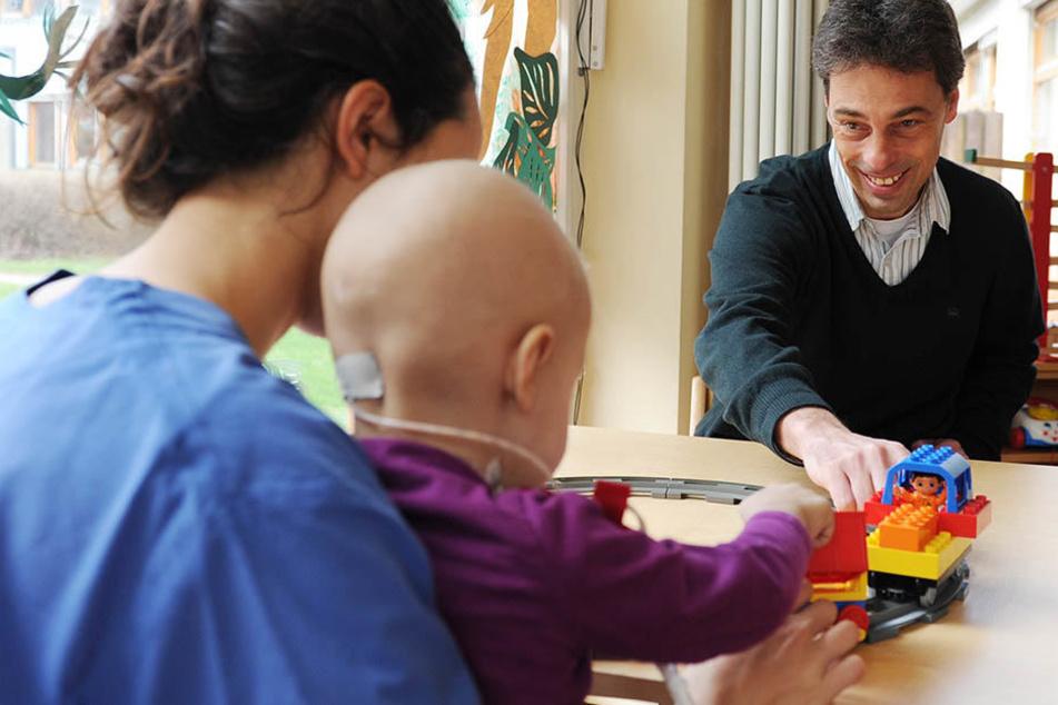 Der Hamburger Kinderonkologe Prof. Stefan Rutkowski mit einer Krankenpflegerin und einem am Krebs erkrankten Kind im Spielzimmer des Universitätskrankenhaus Hamburg-Eppendorf (UKE).