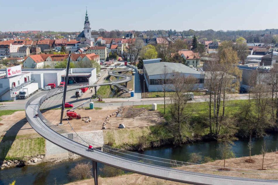 Bauarbeiter sind an einer geschwungenen Schrägseilbrücke mit den letzten Vorbereitungen für die Landesgartenschau in Frankenberg/Sachsen beschäftigt.
