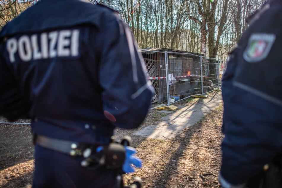 Zwei Beamte der Polizei bei Ermittlungen auf der Parzelle.