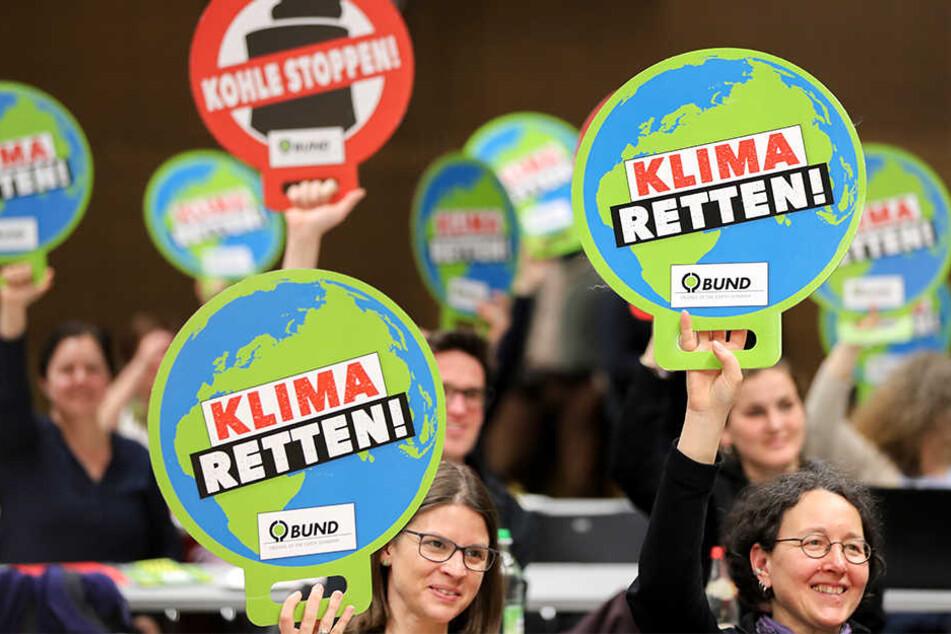 """Die Grünen protestierten mit Schildern mit der Aufschrift """"Klima retten!"""" und """"Kohle stoppen"""" gegen die Abbaggerung des Dorfes Pödelwitz für den Tagebau Vereinigtes Schleenhain."""