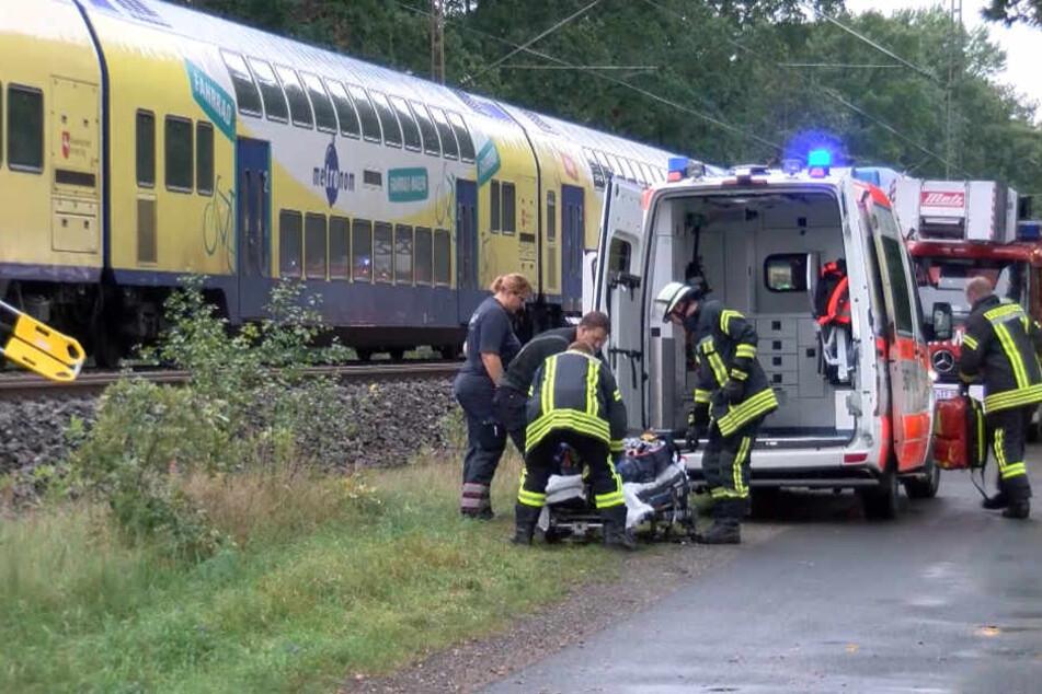 Rettungskräfte bergen einen verletzten Fahrgast bei Oyten (Niedersachsen), nachdem ein Regionalzug gegen einen Baum geprallt war.
