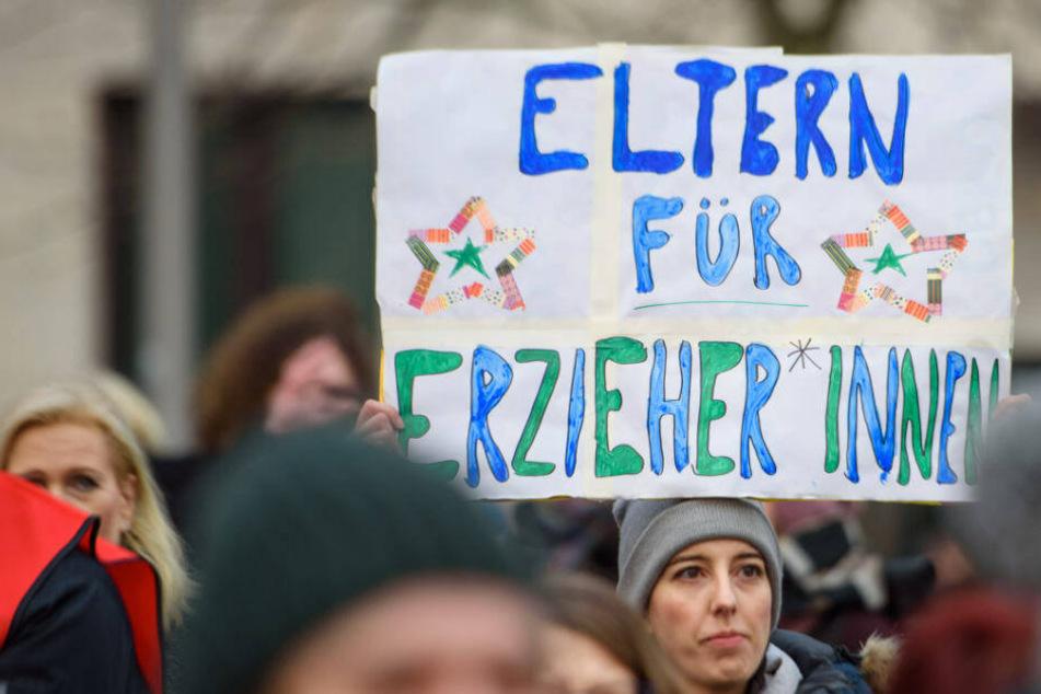 """ErzieherInnen und LehrerInnen und weitere Teilnehmer stehen während eines Warnstreiks mit u.a. mit einem Schild """"Eltern für Erzieher*innen"""" auf dem Dorothee-Schlegel-Platz, um für faire Löhne und bessere Arbeitsbedingungen zu demonstrieren."""