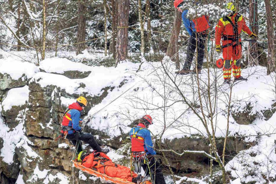 Bestimmt keine Weicheier! Mindestens vier Leute der Bergwacht Dresden seilen einen Verletzten in einer Korbtrage ab - und zwar trotz klirrender Kälte!