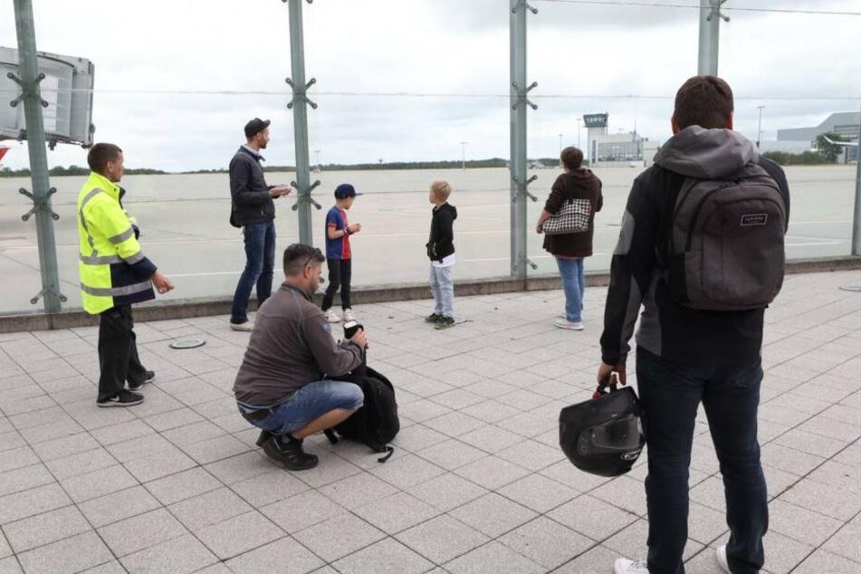 Vereinzelte Schaulustige warten auf den Flieger.