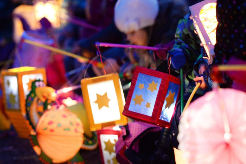 Kinder halten ihren leuchtenden Laternen in die Höhe.