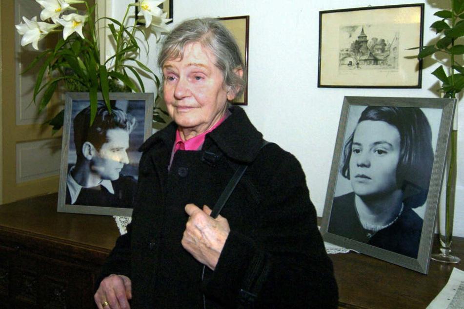 Elisabeth Hartnagel-Scholl steht in der früheren Wohnung ihrer Eltern in Ulm zwischen Fotos ihrer Geschwister Hans und Sophie Scholl.