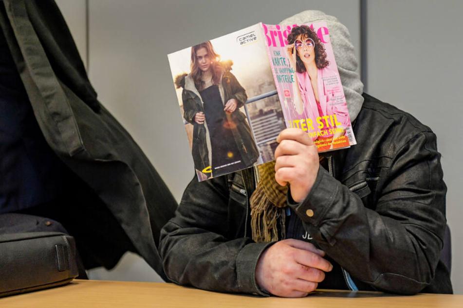Stefan Pries-Schloh verbirgt sein Gesicht vor Gericht hinter einer Illustrierten.