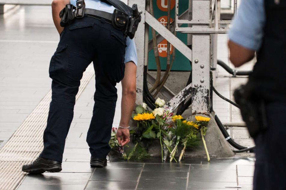Ein Polizist legt am Unglücksort Blumen ab.