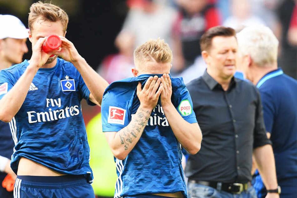 HSV-Spieler Matti Steinmann (l.), Lewis Holtby (m.) und Trainer Christian Titz sind nach der Niederlage in Frankfurt fassungslos.