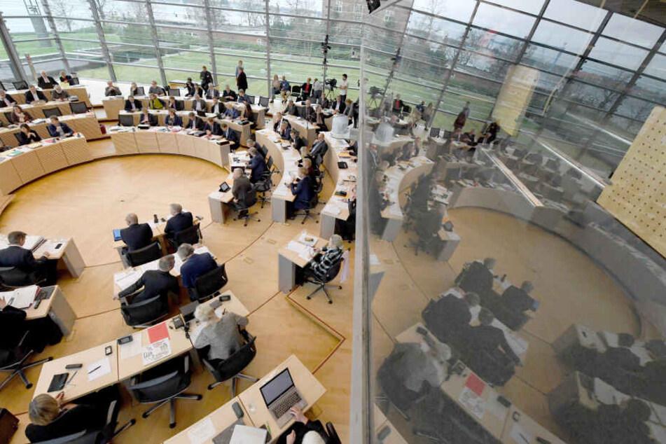 Der Landtagin Kiel während eine Sitzung: Der Parlamentssaal spiegelt sich in der Scheibe der Besuchertribüne.