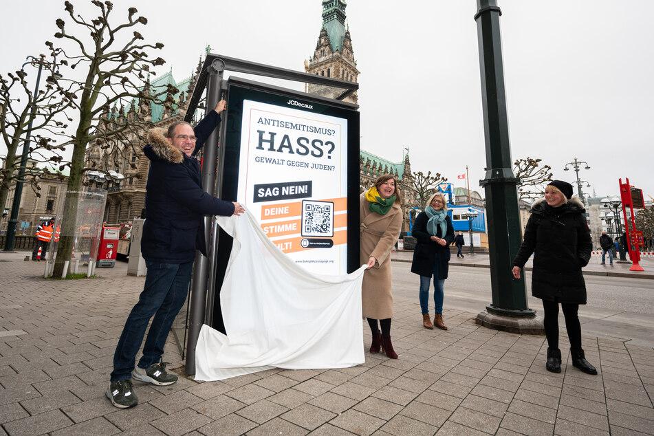 Unterstützer der Initiative enthüllen ein Plakat in der Innenstadt.