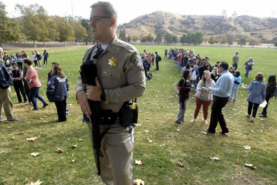 Ein Polizist bewacht Schüler, die von ihren Eltern abgeholt werden sollen.