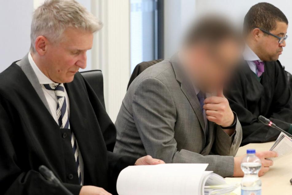 Der Angeklagte Neurochirurg sitzt zwischen seinen Anwälten Temba Hoch (rechts) und Wolf Klink. (Archivbild)