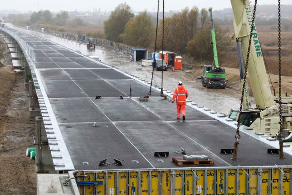 An der Behelfsbrücke für die abgesackte A20 wird das letzte Bauteil verlegt.