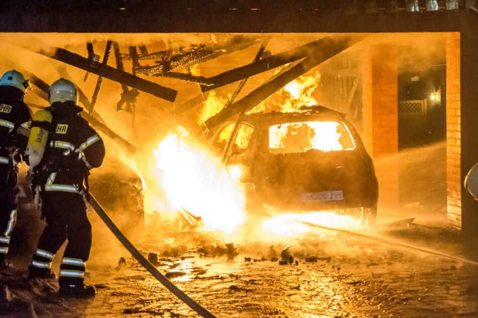 Carports und Auto stehen lichterloh in Flammen. Die Feuerwehr versucht den Brand zu löschen.