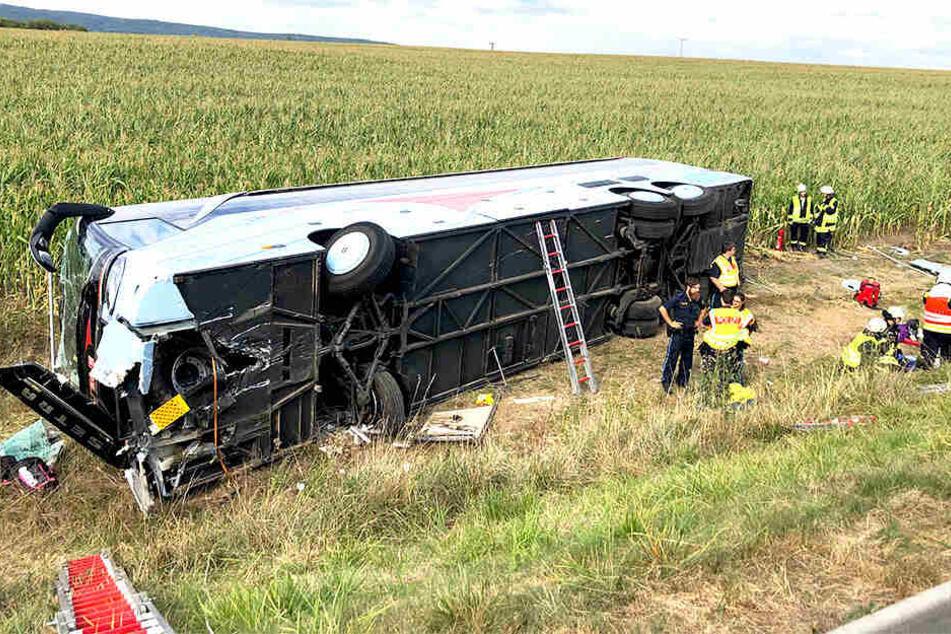 Der umgekippte Bus liegt auf der Seite. Rettungskräfte sind vor Ort.