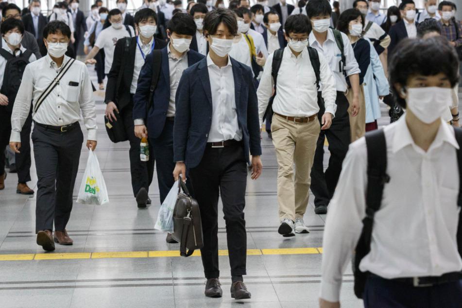 Pendler mit Mundschutz gehen vom Bahnhof Shinagawa zu ihren Büros. Japan hat den Corona-Notstand für das gesamte Inselreich vorzeitig aufgehoben.