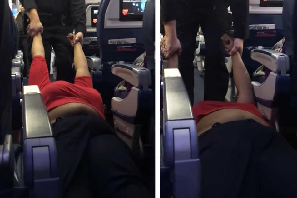 Hier wird eine Frau von einem Polizisten durchs Flugzeug gezerrt