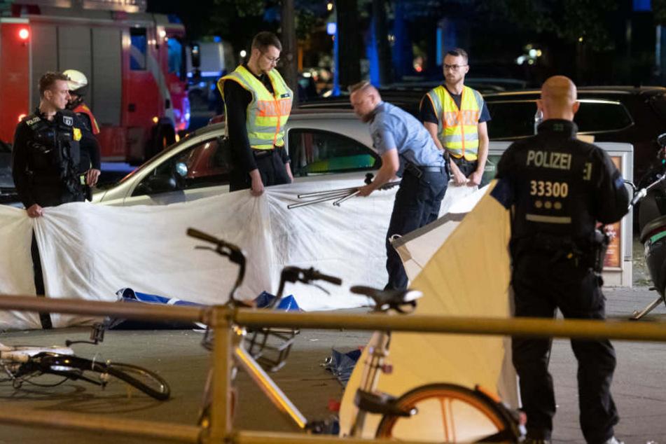 Polizisten errichten einen Sichtschutz für die verunglückte Frau.