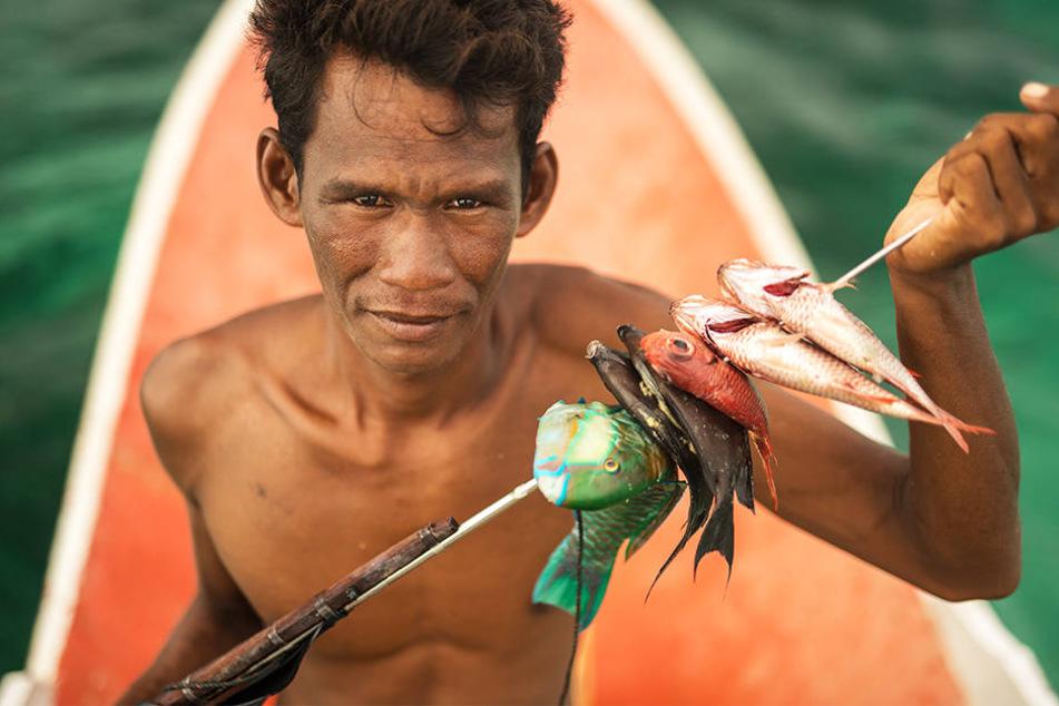 Ein Bajau, Seenomade, der in den Gewässern vor Indonesien lebt, präsentiert seinen Fang. Ihre Existenz wird durch die extreme Überfischung bedroht.